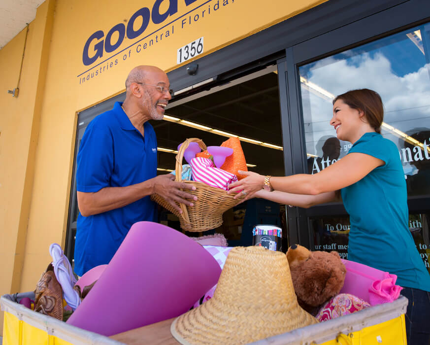two Goodwill volunteers with a basket outside of a Goodwill store