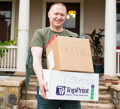 Man smiling with boxes of items to donate to Goodwill