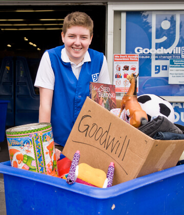 Goodwill worker smiling while collecting donations