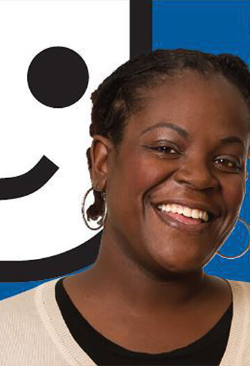 Denitra, a woman smiling, in front of the goodwill logo