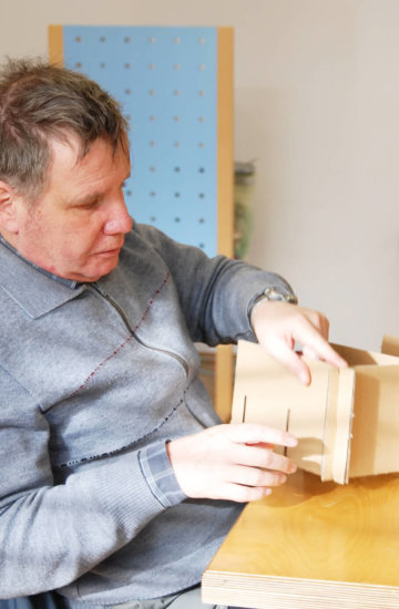 Participant making structure out of cardboard at GoodSource