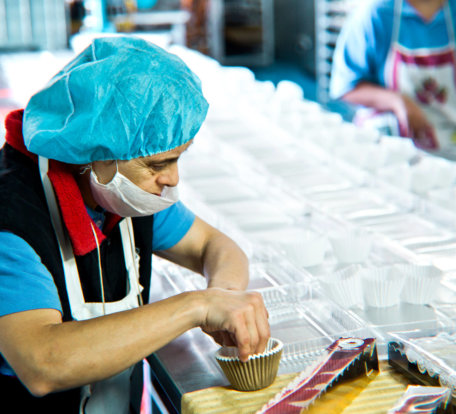 Worker with GoodSource placing Muffin tins in containers