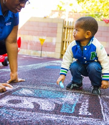 Child drawing Goodwill logo with sidewalk chalk with a goodwill volunteer