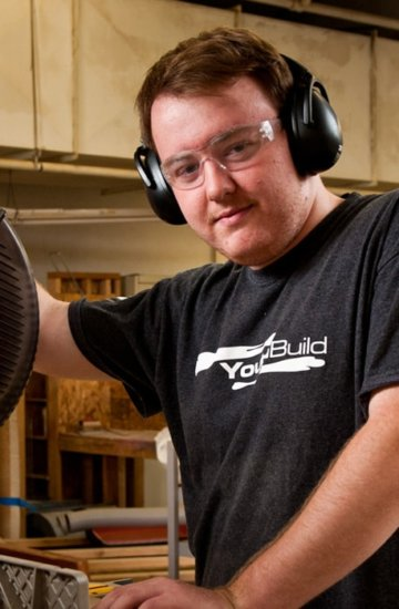 Man working with a miter saw wearing safety equipment