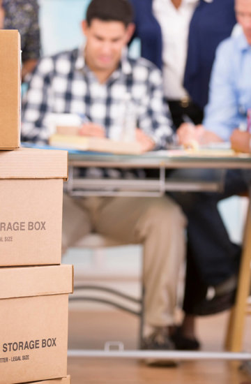 Storage boxes and people working around a table