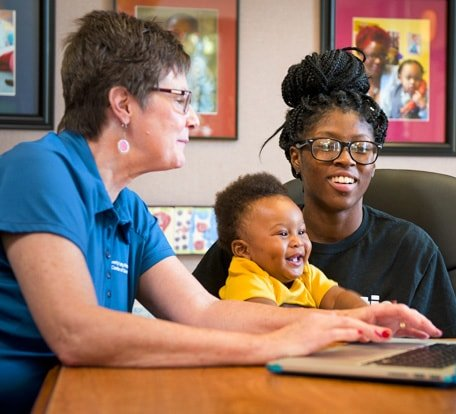 Goodwill volunteer giving computer training to a woman who is holding her smiling baby